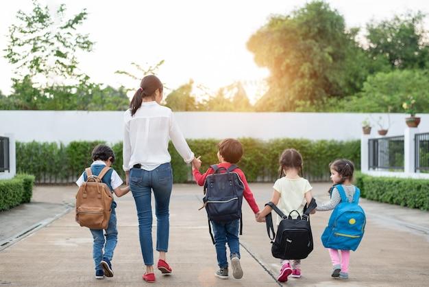 Groupe d'étudiant d'âge préscolaire et enseignant main dans la main et marche à la maison.