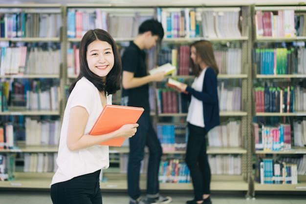 Groupe d'étudiants asiatiques étudient ensemble dans la bibliothèque à l'université.