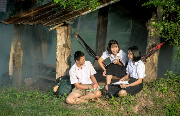 Groupe d'étudiants asiatiques en uniforme étudient ensemble à l'extérieur.