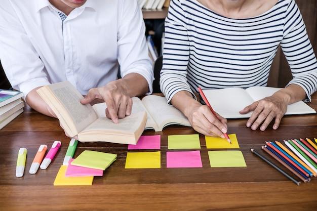 Groupe d'étudiants assis à un bureau dans une bibliothèque étudiant et lisant, faisant ses devoirs et ses leçons