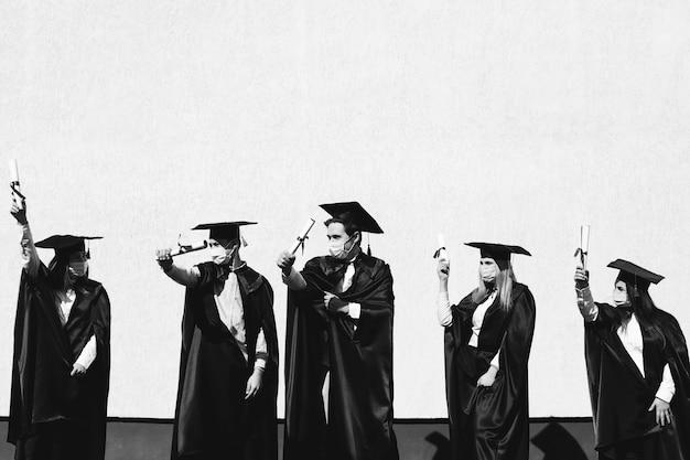 Groupe d'étudiants célébrant ensemble l'obtention du diplôme et portant des masques faciaux