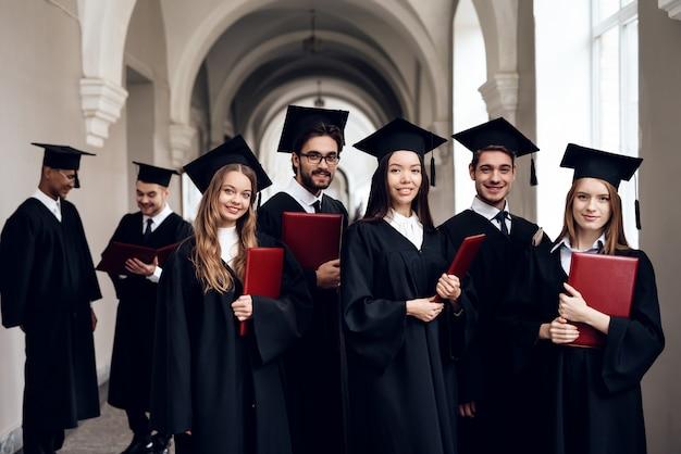 Un groupe d'étudiants dans des manteaux sont debout dans le couloir.