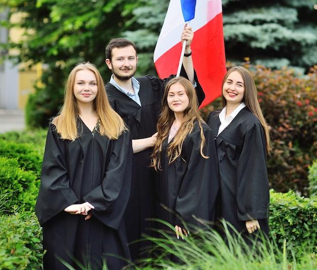 Groupe d'étudiants diplômés de la faculté des langues étrangères en toges tiennent le drapeau de la france dans leurs mains