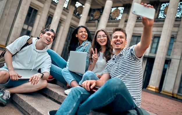 Un groupe d'étudiants est assis sur les marches près du campus avec des ordinateurs portables, se détendant, bavardant et prenant des selfies sur un smartphone.