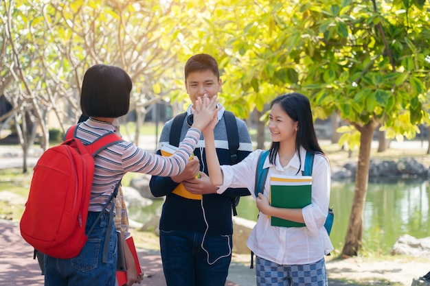 Groupe d'étudiants jeunes heureux toucher les mains à l'extérieur, divers jeunes étudiants livre concept en plein air