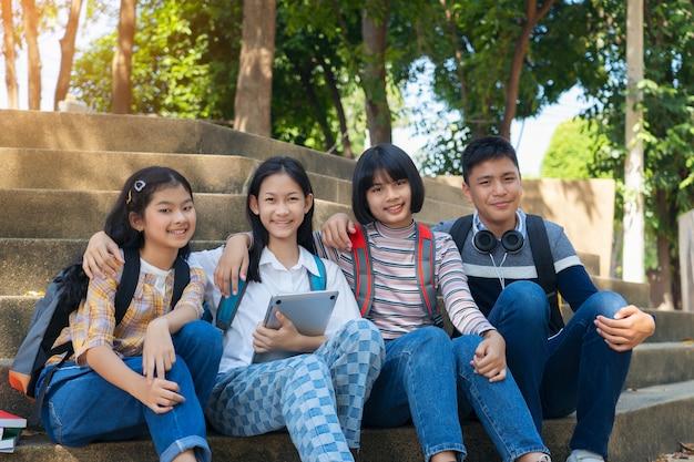Groupe d'étudiants jeunes et livre de lecture de l'éducation dans le parc de la ville