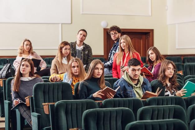 Le groupe d'étudiants joyeux assis dans une salle de conférence avant la leçon.