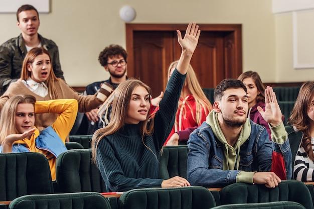 Le groupe d'étudiants joyeux et heureux assis dans une salle de conférence avant la leçon