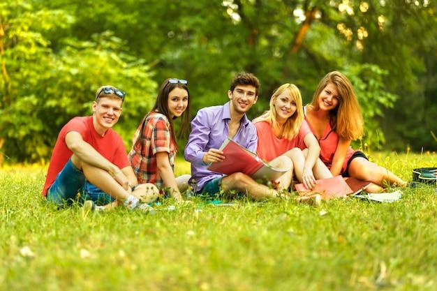 Groupe d'étudiants avec des livres dans le parc par une journée ensoleillée