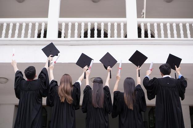 Groupe d'étudiants réussies avec félicitations ensemble jeter des chapeaux de graduation dans l'air et de célébrer. concept de l'éducation.