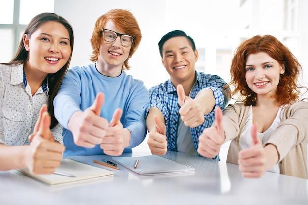 Groupe d'étudiants satisfaits montrant thumbs up