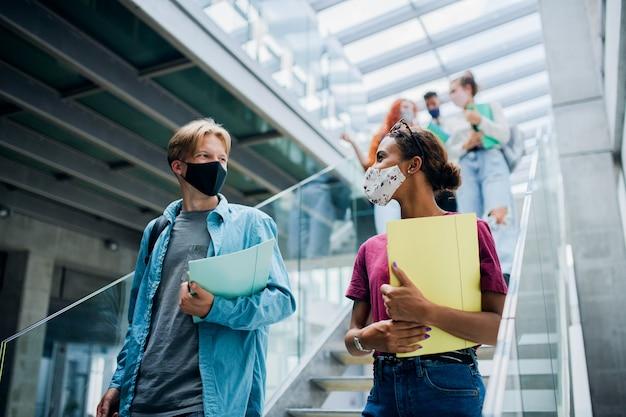 Groupe d'étudiants universitaires descendant les escaliers à l'intérieur du coronavirus et du concept normal de retour