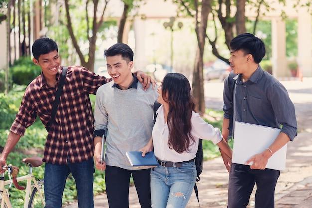 Groupe d'étudiants universitaires marchant à l'extérieur ensemble sur le campus