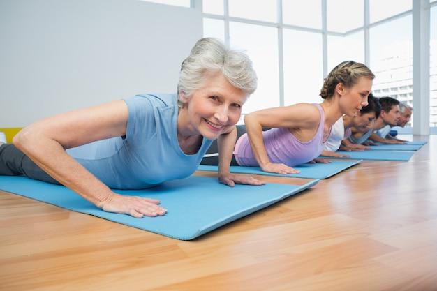 Groupe faisant cobra pose en rangée au cours de yoga