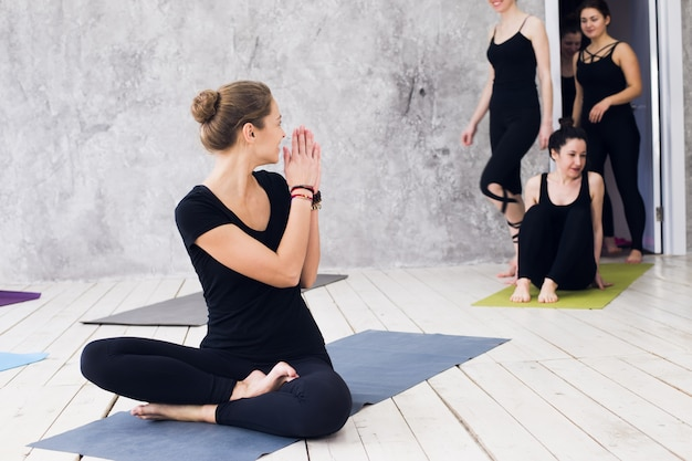Groupe faisant du yoga au gymnase. bienvenue sur le cours de yoga. les exercices commencent à l'intérieur
