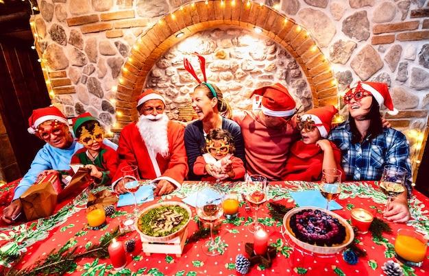 Groupe de famille nombreuse sur plusieurs générations avec des vêtements de chapeaux de père noël s'amusant à la fête de noël