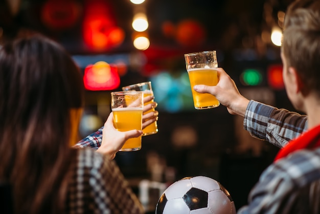 Groupe de fans de football avec de la bière célèbre la victoire de l'équipe favorite au bar des sports. diffusion tv, loisirs de jeunes amis au pub