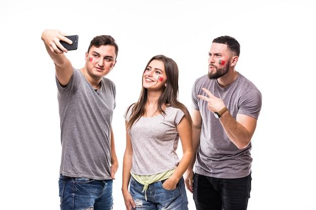 Groupe de fans de football prendre selfie tout en soutenant l'équipe nationale du portugal sur fond blanc. concept de fans de football.