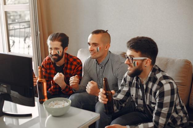 Un groupe de fans regarde le football à la télévision