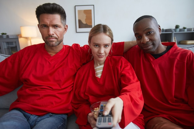 Groupe de fans de sport portant du rouge tout en regardant un match à la maison et en tenant la télécommande