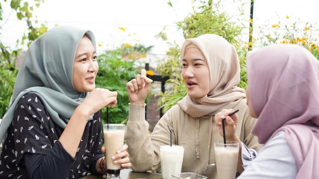 Groupe de femme asiatique hijab souriant au café avec un ami