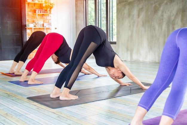 Groupe de femmes asiatiques fitness échauffement pose de yoga en rangée à la classe de yoga. mise au point sélective