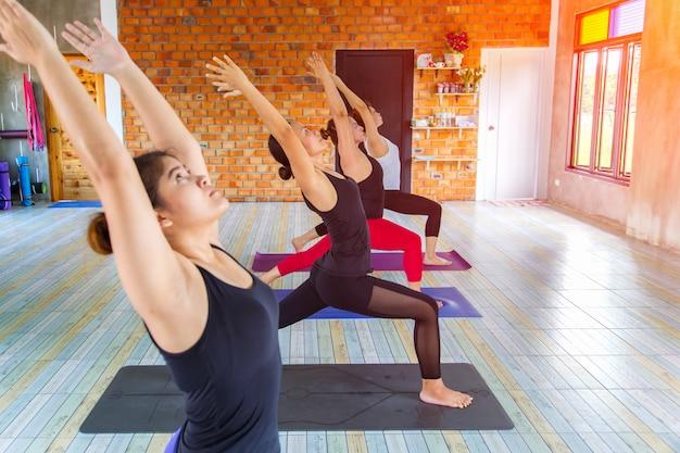 Groupe de femmes asiatiques fitness échauffement pose de yoga en rangée à la classe de yoga.
