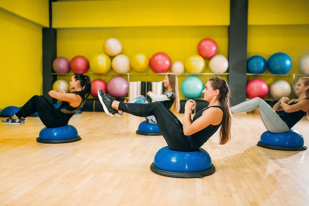 Groupe de femmes athlétiques en vêtements de sport s'exerçant sur l'entraînement physique. travail d'équipe de sport féminin dans la salle de gym. exercice d'ajustement en mouvement