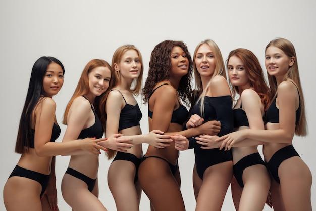 Groupe de femmes au corps et à l'ethnie différents posant ensemble pour montrer le pouvoir et la force de la femme.