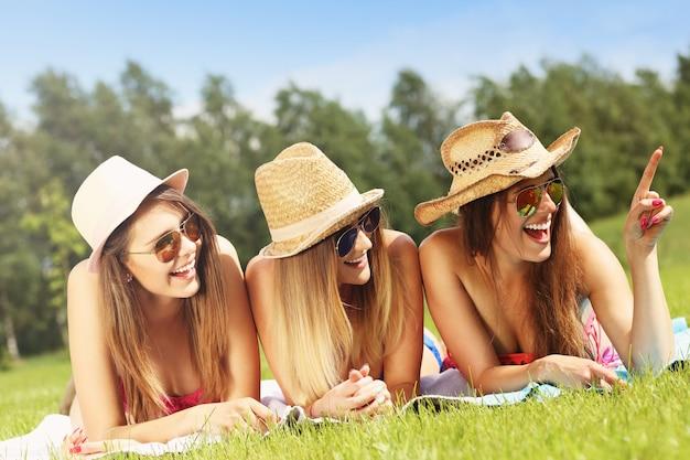 Un groupe de femmes en bikin montrant quelque chose à l'extérieur