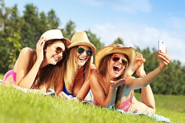 Un groupe de femmes en bikini prenant un selfie à l'extérieur