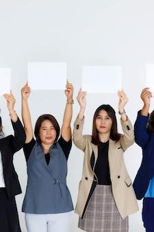 Un groupe de femmes de bureau dans les affaires porte un support de prise de vue en studio sur le visage de couverture de signe de papier vide vierge pour le texte de la publicité sur fond blanc.
