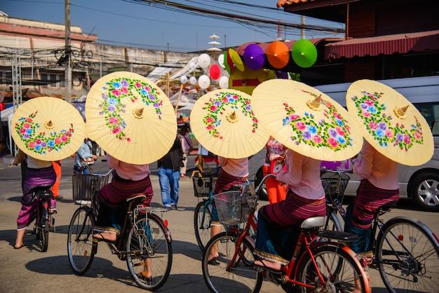 Un groupe de femmes en costume traditionnel tient un parapluie et fait un défilé à vélo spectacle bo chante un parapluie