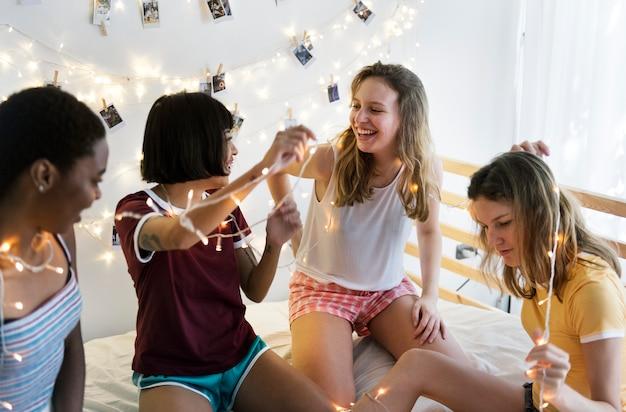 Groupe de femmes diverses s'amusant sur le lit ensemble