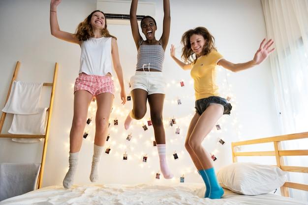Un groupe de femmes diverses sautant sur le lit ensemble