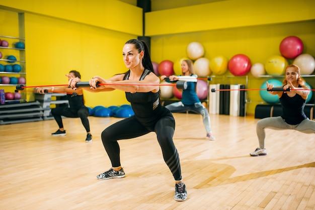 Groupe de femmes sur l'entraînement physique, aérobie. travail d'équipe de sport féminin dans la salle de gym.