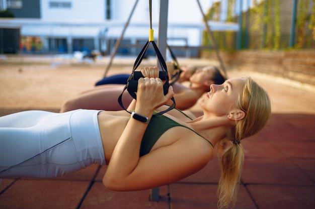 Groupe de femmes, exercice avec des cordes sur un terrain de sport, vue de face, entraînement de remise en forme en plein air