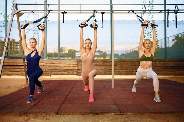 Groupe de femmes faisant de l'exercice de remise en forme avec des cordes sur un terrain de sport, formation en plein air