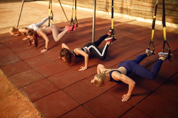 Groupe de femmes faisant des pompes sur un terrain de sport, vue de face, entraînement de remise en forme en plein air