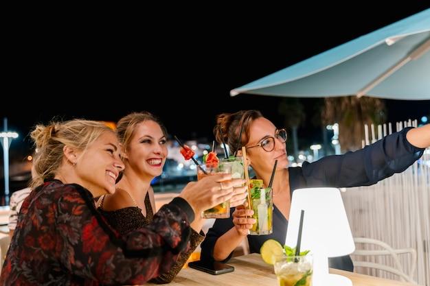 Groupe de femmes faisant un selfie assis sur une terrasse en buvant des cocktails la nuit