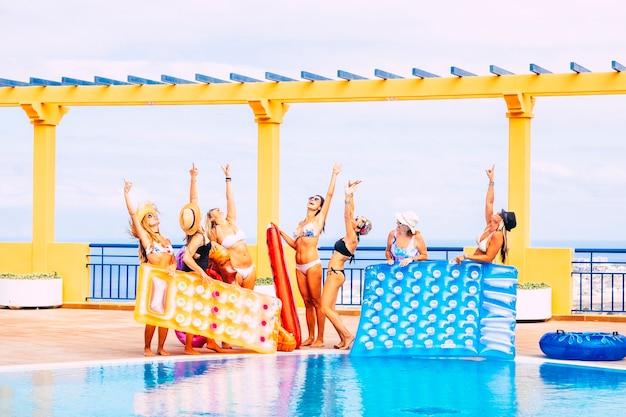 Un groupe de femmes heureuses profitent ensemble de la piscine d'eau bleue avec un bikini et des lilos colorés et s'amusent en amitié
