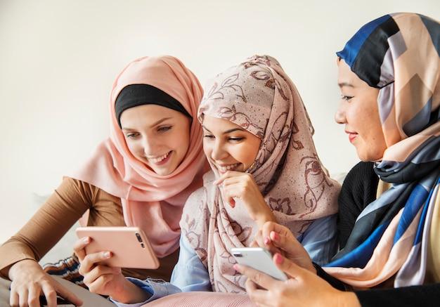 Groupe de femmes islamiques parlant et regardant au téléphone ensemble