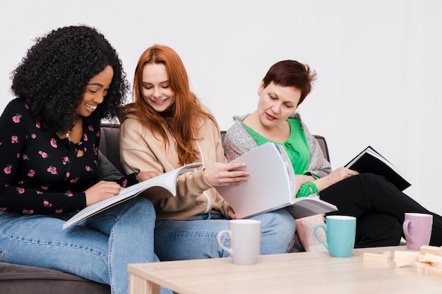 Groupe de femmes lisant un livre ensemble