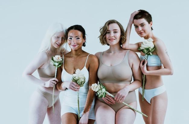 Groupe de femmes multiethniques avec différents types de peau posant ensemble en studio concept sur le corps