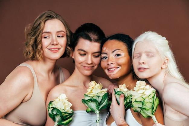 Groupe de femmes multiethniques avec différents types de peau posant ensemble en studio. concept sur la positivité corporelle et l'acceptation de soi