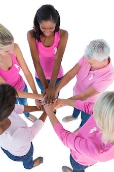 Groupe de femmes portant des roses et des rubans pour le cancer du sein mettant les mains ensemble
