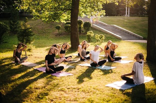 Un groupe de femmes s'étire le cou dans le parc de la ville le matin ensoleillé d'été sous la direction d'un instructeur