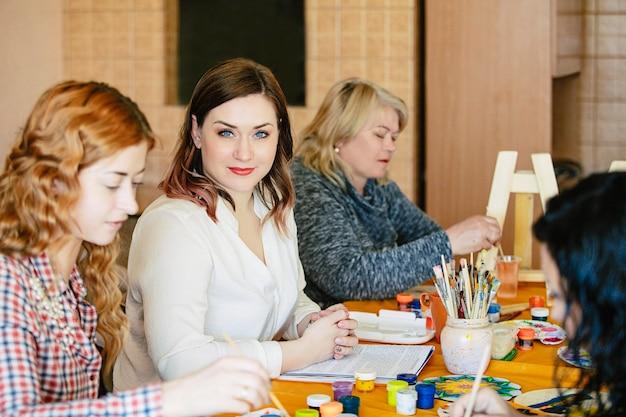 Groupe de femmes souriantes et heureuses lors de la formation artistique sur la création de la vie de mandala