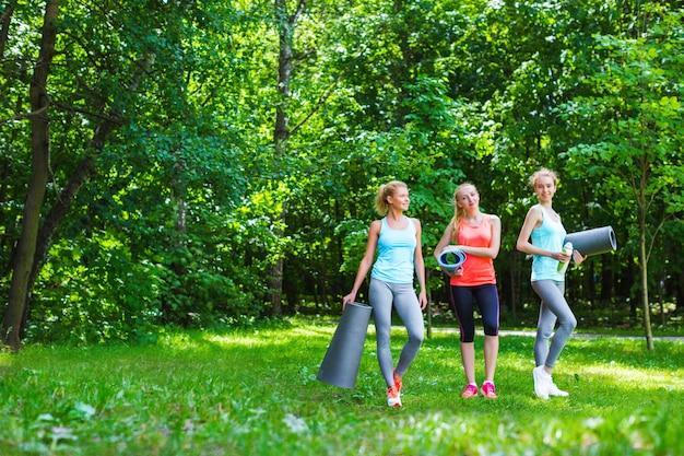 Groupe de femmes de sport dans le parc avec des tapis de yoga