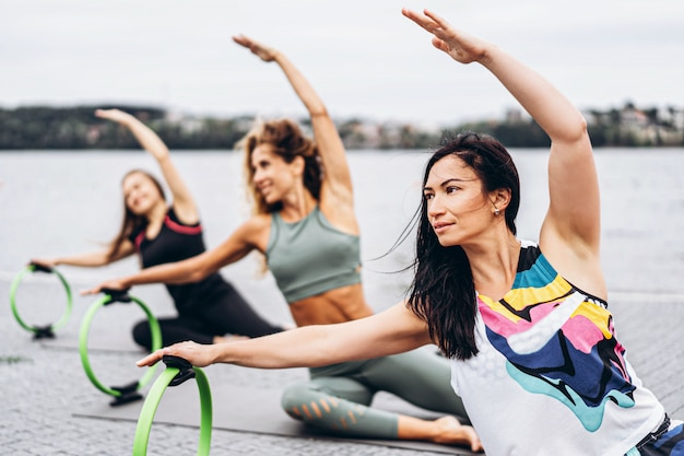 Groupe de femmes sportives faisant des exercices d'étirement avec un cercle sportif spécial dans la rue près de l'eau.